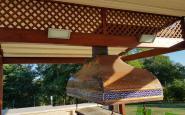 cappa in rame e ceramica sotto al gazebo in legno con grigliato sottostante la copertura