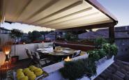 pergotenda in legno scuro appoggiata su parapetto del terrazzo con copertura a scorrimento motorizzato